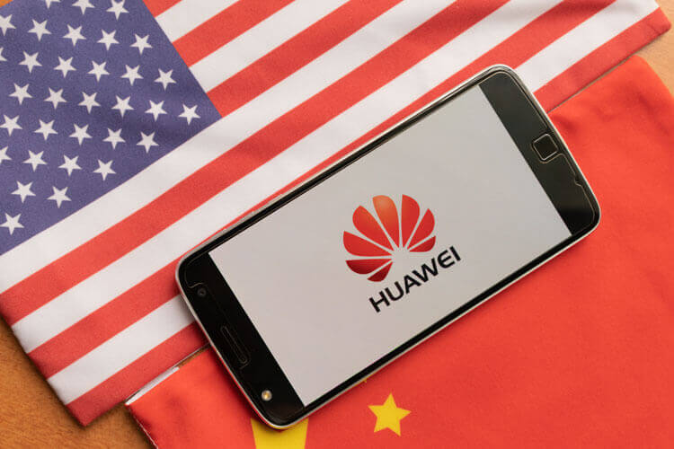 Huawei logo on a smartphone with the American and Chinese flags